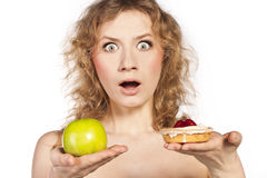 Young woman, choosing apple and cake Royalty Free Stock Images