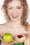 Young woman, choosing apple and cake Stock Photo