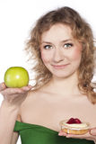 Young woman, choosing apple and cake Stock Photography