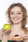Young woman, choosing apple and cake Stock Photos