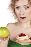 Young woman, choosing apple and cake Royalty Free Stock Photo