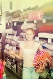 Young woman choosing blanket. In bedding section in shop Royalty Free Stock Image