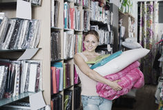 Young woman choosing blanket and pillow. Portrait of young woman choosing blanket, pillow and textile in bedding section in shop Royalty Free Stock Image