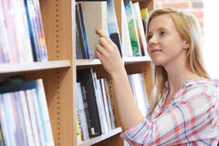 Young Woman Choosing A Book In Bookstore. Woman Choosing A Book In Bookstore Stock Photo