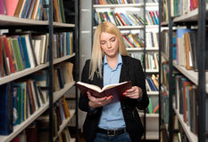 Young woman choosing a book in the library Stock Images