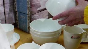 Young woman is choosing bowl in utensils section. Inside The bay store stock video