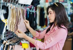 Woman choosing and buying bra in shopping store royalty free stock photography