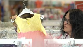 Young woman choosing children`s clothes for child at baby shop store in mall. Family shopping, mother looking at, buying. Young woman choosing children`s clothes stock video footage