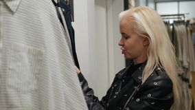 Young woman choosing clothes on a rack in a showroom shopping mall store. Young woman choosing clothes on a rack in a showroom stock video
