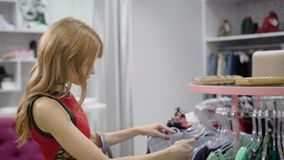Young woman choosing clothes. Side view of beautiful female with wavy hair wearing red dress shopping at trendy boutique stock video footage