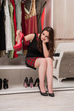 The young woman choosing clothing for evening party. Young woman choosing clothing for evening party Stock Photography