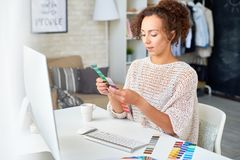 Young Woman Choosing Color Palette. Portrait of creative young woman looking at color swatches choosing palette for home interior design stock image