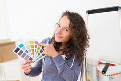 Young woman choosing colors of their new flat Royalty Free Stock Photo