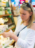 Young woman choosing cosmetic cream. Royalty Free Stock Image