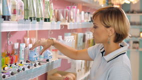 Young woman choosing cosmetic cream in beauty shop. Stock Images