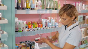 Young woman choosing cosmetic cream in beauty shop. Stock Photos