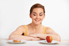 Young Woman Choosing Between Doughnut And Cake For Snack Royalty Free Stock Photography