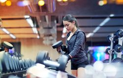 Young woman choosing dumbbells in gym Royalty Free Stock Images