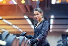 Young woman choosing dumbbells in gym Stock Image