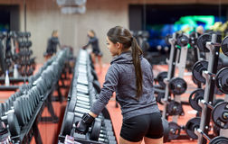 Young woman choosing dumbbells in gym Stock Photo