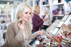 Young woman choosing face powder Stock Image