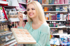 Young woman choosing face powder Stock Photo
