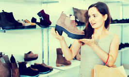 Young woman choosing fall boots in shoes store Royalty Free Stock Photography