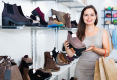 Young woman choosing fall boots in shoes store Royalty Free Stock Photo
