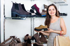 Young woman choosing fall boots in shoes store Stock Photography