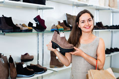 Young woman choosing fall boots in shoes store Royalty Free Stock Image