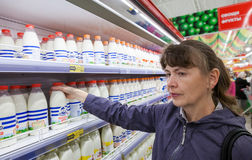 Young woman choosing fresh milk produces Stock Images