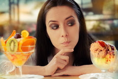 Young Woman Choosing Between Fruit Salad and Ice Cream Desserts Stock Photography