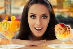 Young Woman Choosing Between Fruit Salad and Ice Cream Desserts Royalty Free Stock Photos