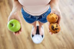 Young woman choosing between fruit and sweet on weighing scale at home. Diet concept. royalty free stock photos