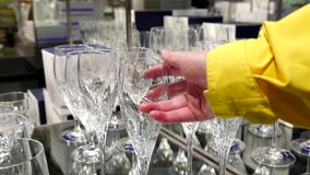 Young woman is choosing glass in utensils section stock video