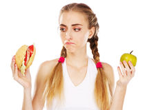 Young woman choosing between hamburger and apple Royalty Free Stock Image