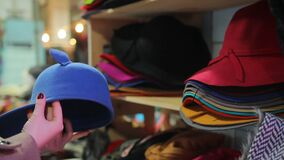 Young woman choosing hats from large seasonal assortment at department store. Stock footage stock footage