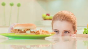Young woman choosing between healthy food and not stock footage