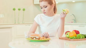 Young woman choosing between healthy food and not stock video