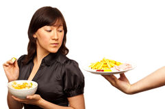 Young woman choosing between healthy salad and fri Royalty Free Stock Photos