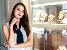 Young woman choosing jewelry in shop. Beautiful girl with long dark hair chooses jewellery in the shop window Royalty Free Stock Images