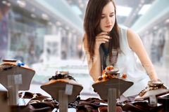 Young woman choosing jewelry in shop. Young woman with long dark hair selects a piece of jewellery in the shop window Stock Photos