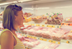 Young Woman Choosing Meat. Royalty Free Stock Images