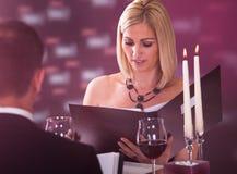 Young woman choosing menu Royalty Free Stock Photo