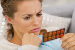 Young woman choosing pills Stock Image
