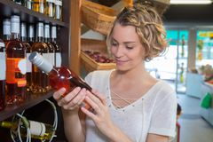 Young woman choosing rose wine in liquor store royalty free stock images