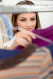 Young woman choosing shirt in clothes shop Stock Photography