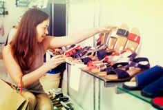 Young woman choosing shoes in store Royalty Free Stock Photos