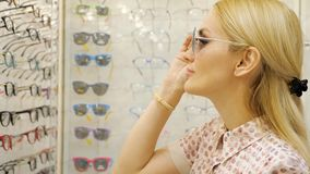 Young woman is choosing a solar glasses in optician store stock video