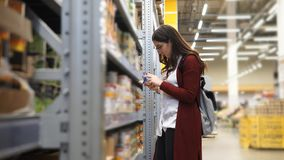 Young woman choosing tins of corn in a hypermarket. She carefully examines the composition of each of the tins, considering the label stock video